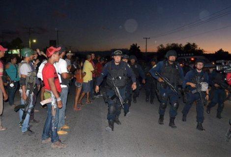 Self-defense groups in La Ruana, Michoacán watch as Federal Police patrol in March 2014. Photo: European Pressphoto Agency.